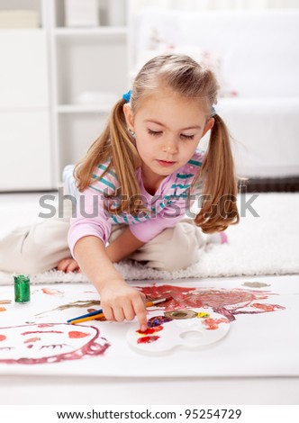 Little girl painting with finger sitting on the floor - stock photo