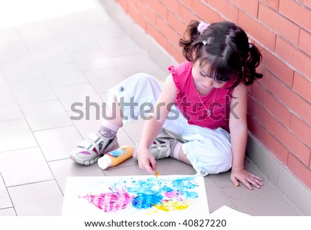 Little girl painting with fingers - stock photo