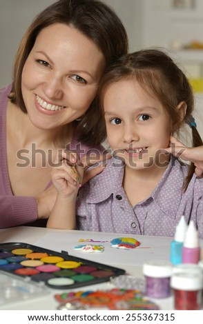 Little girl painting with her mother - stock photo