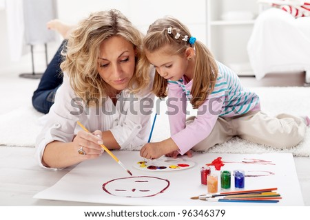 Little girl painting with her mother laying on the floor - stock photo