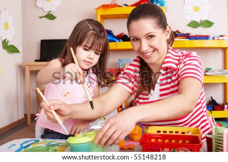 Little girl painting with mother  in preschooler. - stock photo