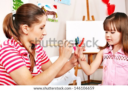 Little girl painting  with teacher in preschool. - stock photo