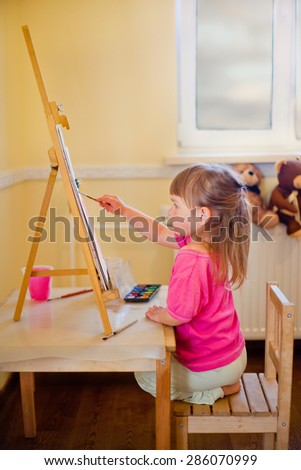 Little girl painting with watercolor on canvas standing on a wooden table easel  - stock photo