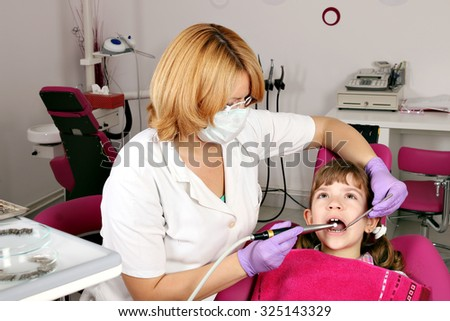 little girl patient and female dentist - stock photo