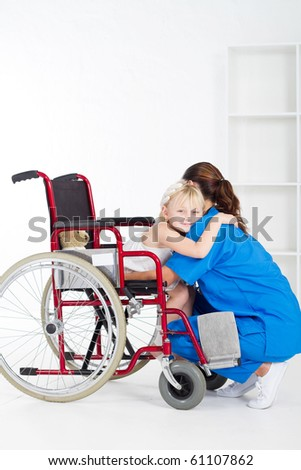 little girl patient on wheelchair hugging doctor - stock photo