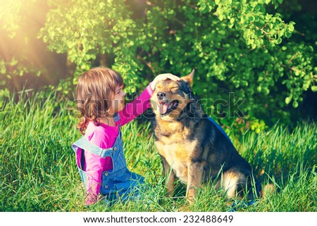 Little girl pats her dog in the forest - stock photo