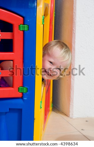 little girl peaks out of small toy house - stock photo