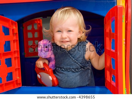 little girl peaks out the window of toy house
