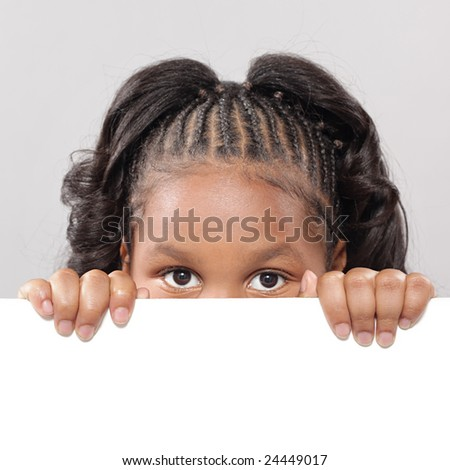 Little girl peeking from behind copy space - stock photo
