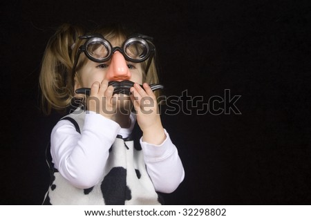 Little girl peeking out from behind silly mustache disguise - stock photo