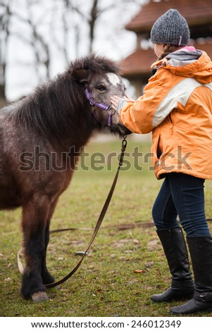 Little girl petting her best friend pony at countryside outdoors - stock photo