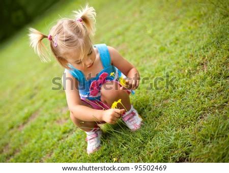little girl picking flowers - stock photo