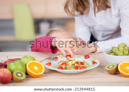 Little girl picking fruit salad from the plate by cropped mother in the kitchen