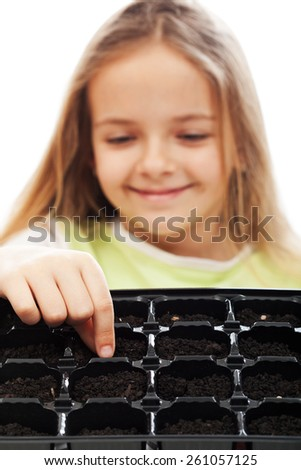 Little girl planting putting seeds into germination tray - growing food concept - stock photo