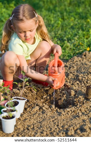 Little girl planting tomato seedlings - preparing the soil - stock photo