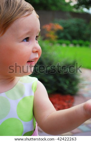 Little girl play on the yard. She look ahead and smile. Her hand direct to her view. Maybe she give some somebody? - stock photo