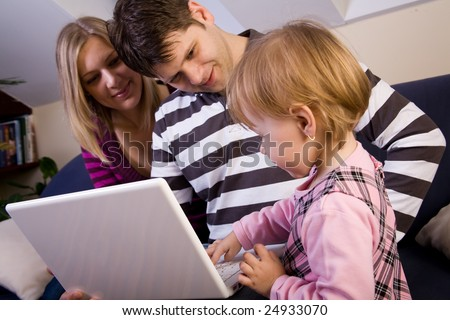 Little girl play with a white laptop with parents
