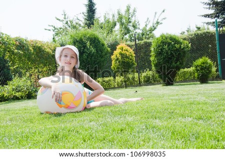 little girl play with ball in park
