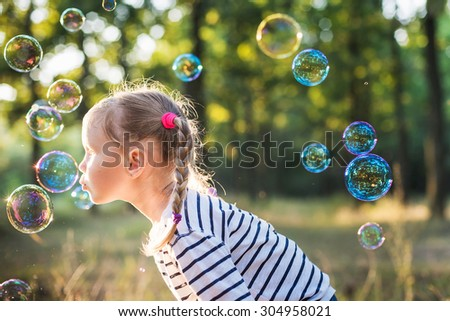 little girl play with bubble blower in the park