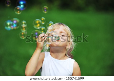 little girl play with bubble blower on green lawn