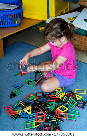 Little girl play with building toy in a play room. Concept photo of preschool education of creativity and thinking - stock photo