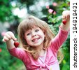 little girl play with fresh strawberry on  nature backgraund - stock photo