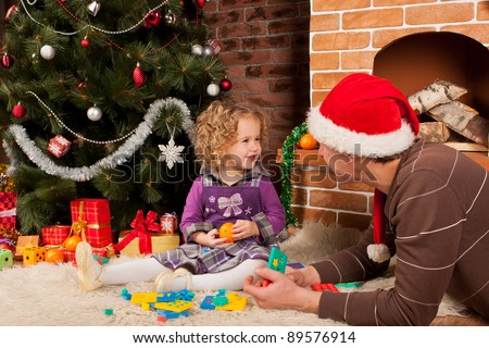 Little girl play with her dad  near Christmas tree