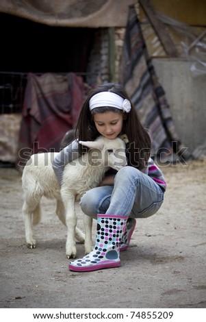 Little girl play with newborn lamb in a farmyard - stock photo