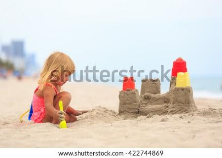little girl play with sand on beach - stock photo