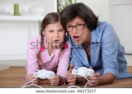 Little girl playing a computer game with her grandma - stock photo