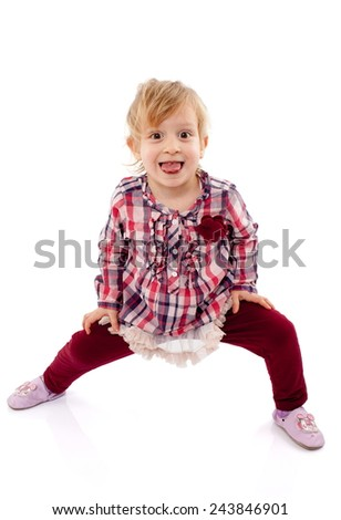 Little girl playing and having fun showing her tongue - stock photo