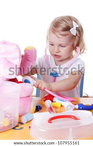 Little girl playing as doctor with stethoscope on white