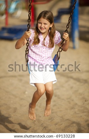 Little girl playing at a park swinging - stock photo
