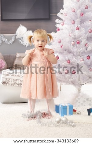 Little girl playing at christmas tree.