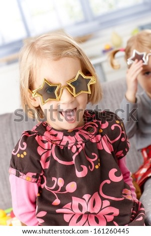 Little girl playing at home, sticking tongue wearing funny star shaped glasses.