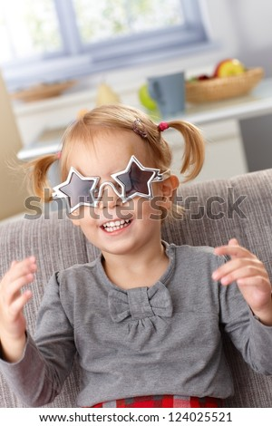 Little girl playing at home, wearing star shaped glasses, smiling. - stock photo