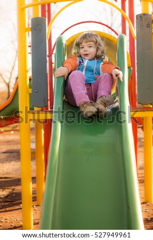 Little Girl Playing At Playground In A Sunny Late Autumn Day