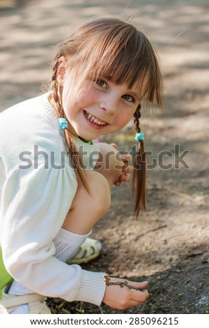 Little girl playing at sand painting stick.