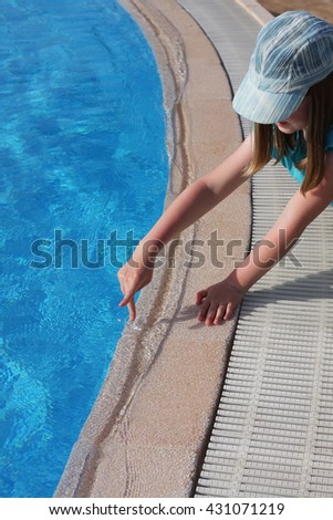 Little girl playing at the edge of the swimming pool, walking her fingers, as though walking on the beach. Concept of dreams about vacation. Soon we will go on holiday and see the sea.  - stock photo