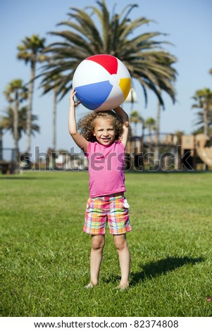 Little girl playing at the park with a beach ball - stock photo