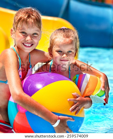 Little girl  playing ball in swimming pool. - stock photo