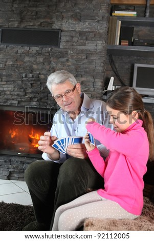 Little girl playing card game with granddad - stock photo