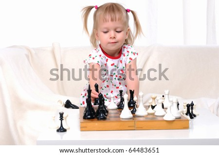 Little girl playing chess at a table