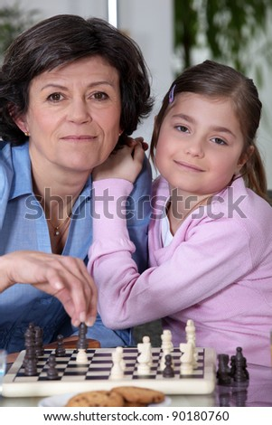 Little girl playing chess with grandmother - stock photo
