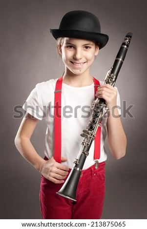 little girl playing clarinet on a gray background - stock photo