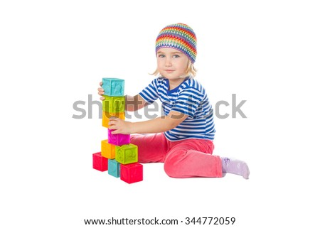 Little girl playing cubes sitting . Isolated on a white background. - stock photo
