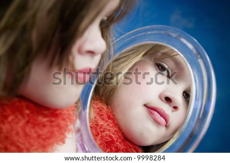 Little Girl Playing Dress-Up Looking in a Handheld Mirror - stock photo