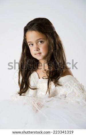 Little girl playing dress up with adult wedding dress, 7 yrs old, brunette - stock photo