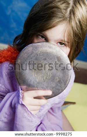 Little Girl Playing Dress-Up with an Antique Handheld Mirror - stock photo