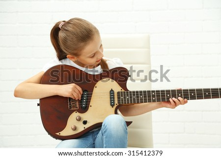 Little girl playing guitar on light background - stock photo